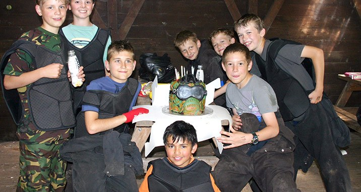 Friends get together to enjoy a kids birthday cake inspired by paintball.