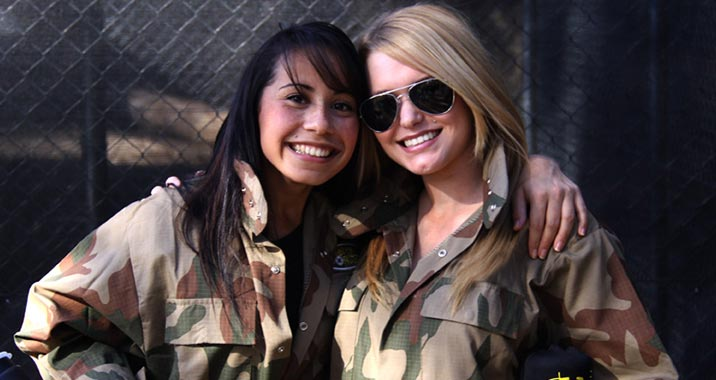 Two girls posing together after a great game of paintballing.